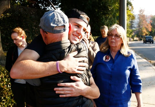 Activist Lonnie Phillips hugs shooting survivor Ben Campbell at a police barricade near the mass shooting site at the Borderline Bar and Grill on Friday, Nov. 9, 2018, in Thousand Oaks, Calif. Phillips lost his daughter, Jessica Ghawi, when she was mudered in a movie theater shooting in Aurora, CO. Campbell survived after twelve people were shot and killed Wednesday by gunman Ian David Long who opened fire at the Borderline Bar and Grill.