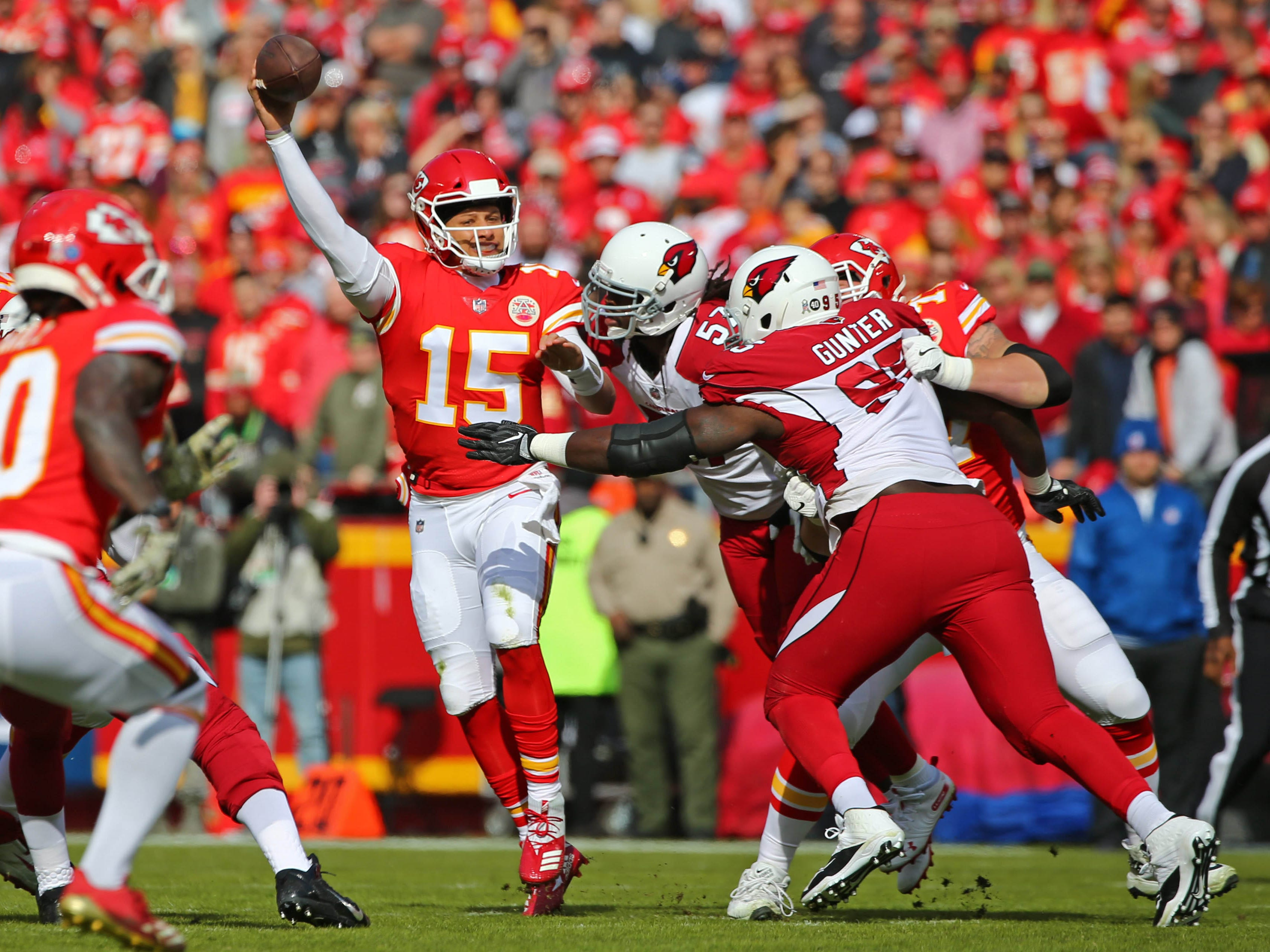 Nov 11, 2018; Kansas City, MO, USA; Kansas City Chiefs quarterback Patrick Mahomes (15) throws a pass as Arizona Cardinals linebacker Josh Bynes (57) and defensive tackle Rodney Gunter (95) defend in the first half at Arrowhead Stadium. Mandatory Credit: Jay Biggerstaff-USA TODAY Sports
