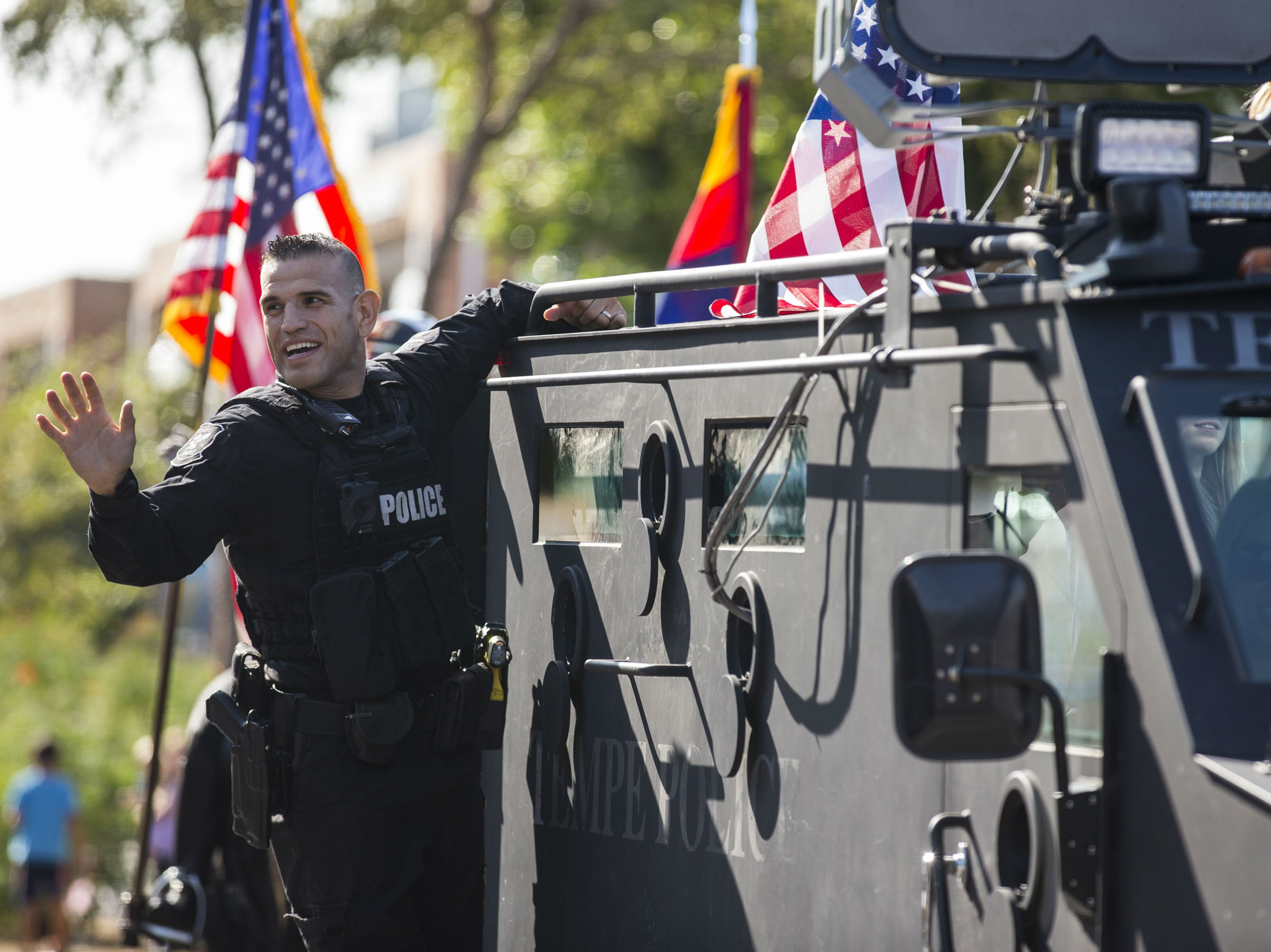 A Tempe Police Department officer waves to the crowd during the Veterans Day Parade on Nov. 11,  2018, in Tempe, Ariz.