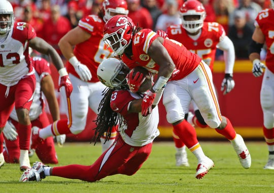 Nov 11, 2018; Kansas City, MO, USA; Kansas City Chiefs running back Kareem Hunt (27) is tackled by Arizona Cardinals safety Tre Boston (33) in the first half at Arrowhead Stadium. Mandatory Credit: Jay Biggerstaff-USA TODAY Sports