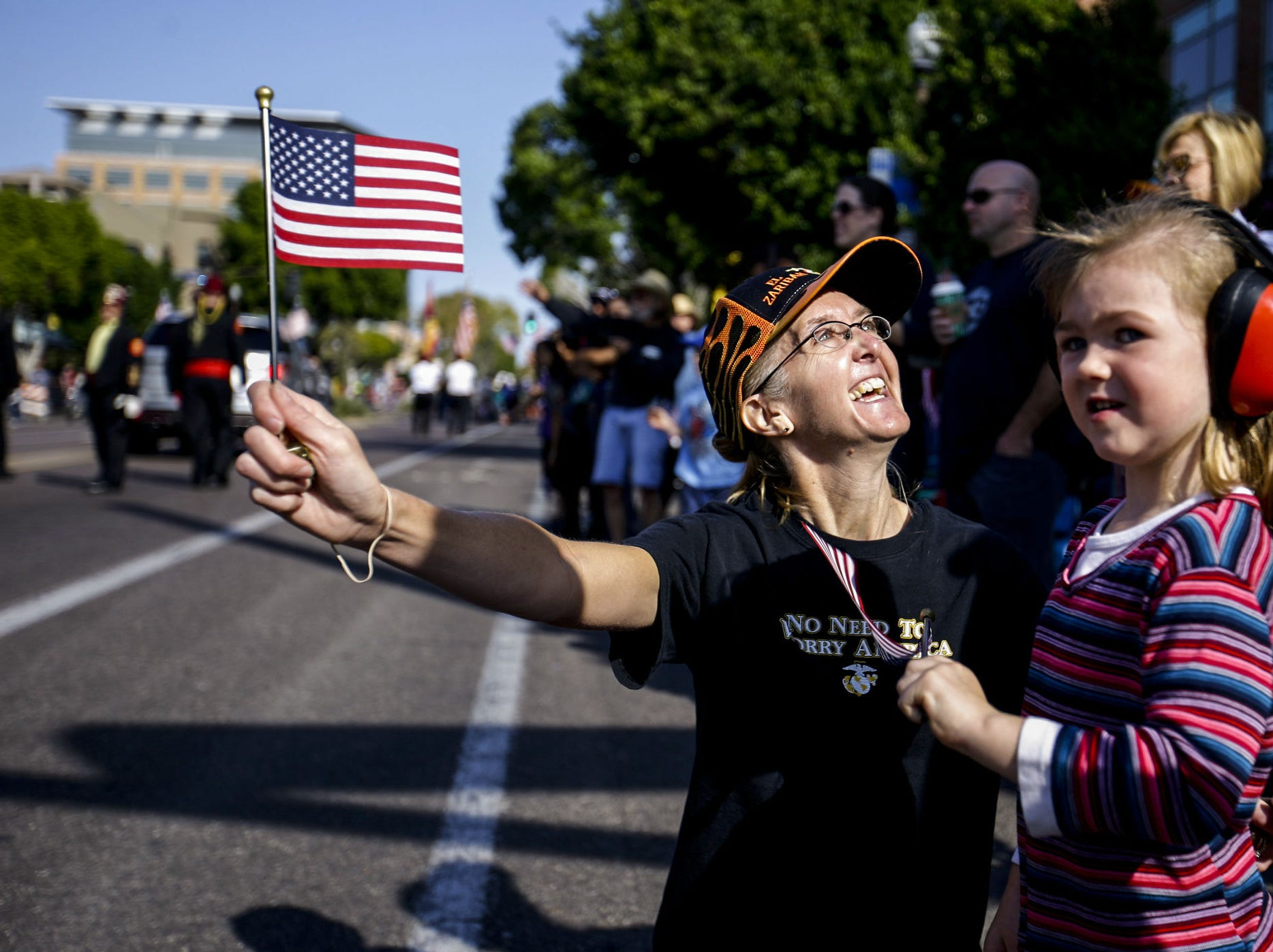 Melissa Greene and her granddaughter, Lily Lahti, watch the Veterans Day Parade on Nov. 11, 2018, in Tempe, Ariz.