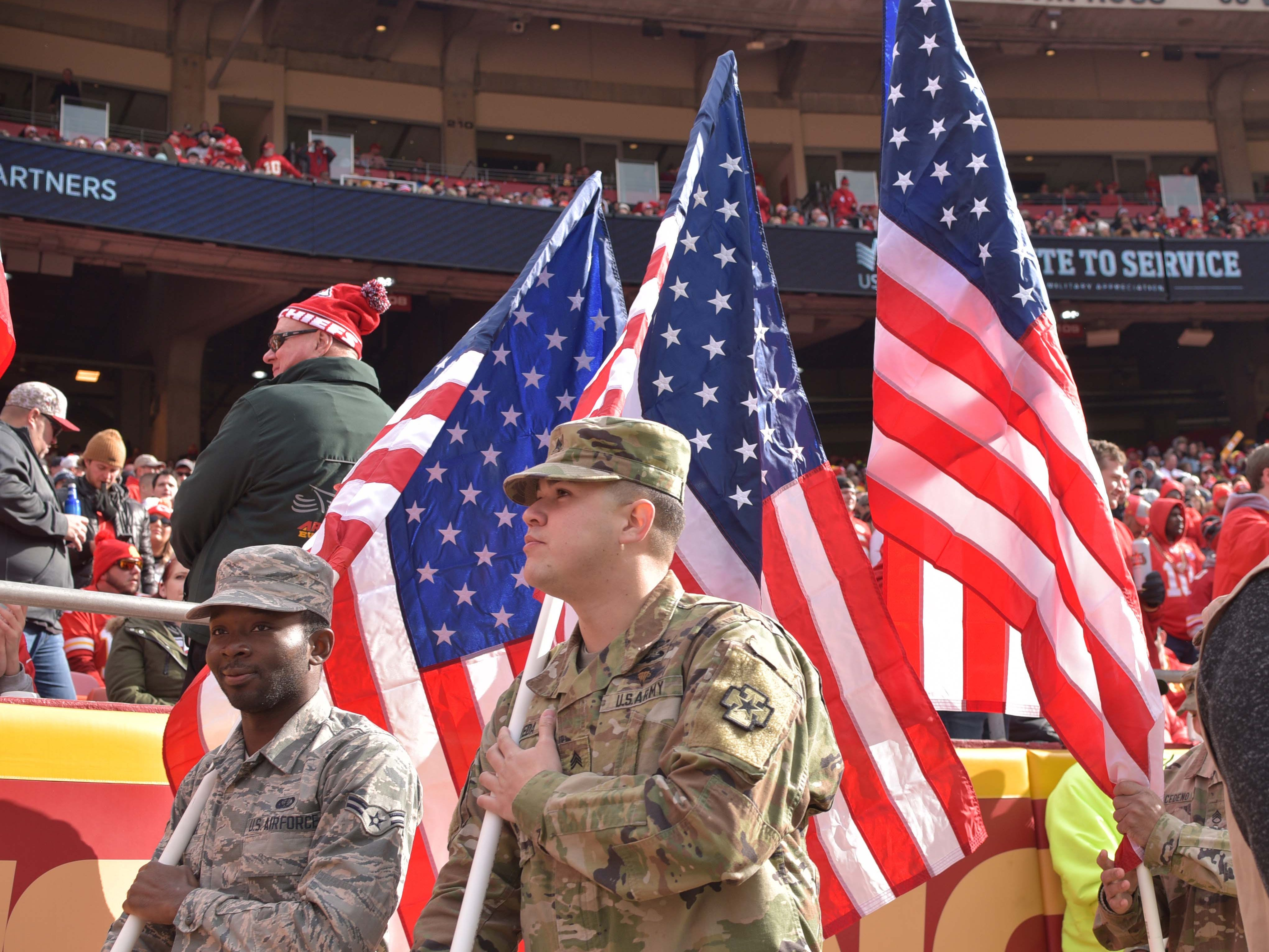 Nov 11, 2018; Kansas City, MO, USA; Armed forces service members carry American flags on the sidelines in preparation for the half-time Salute to Service activities during the first half of the game between the Kansas City Chiefs and Arizona Cardinals at Arrowhead Stadium. Mandatory Credit: Denny Medley-USA TODAY Sports