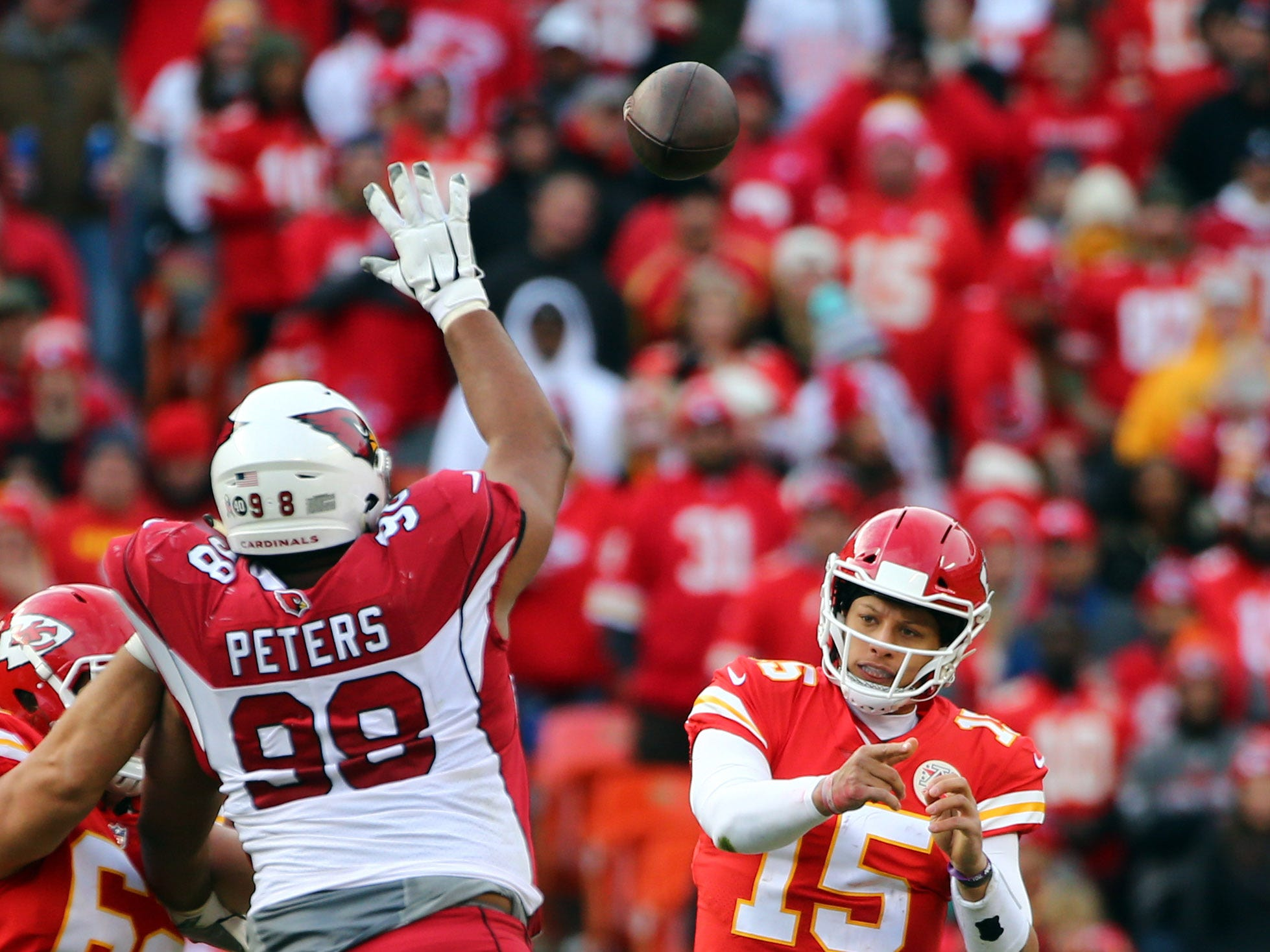 Nov 11, 2018; Kansas City, MO, USA; Kansas City Chiefs quarterback Patrick Mahomes (15) throws a pass as Arizona Cardinals defensive tackle Corey Peters (98) defends in the second half at Arrowhead Stadium. Mandatory Credit: Jay Biggerstaff-USA TODAY Sports