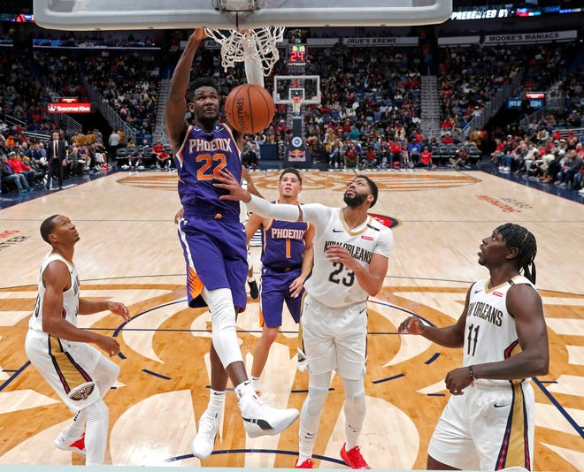 Phoenix Suns center Deandre Ayton (22) slam dunks over New Orleans Pelicans forward Wesley Johnson, left, forward Anthony Davis (23) and guard Jrue Holiday (11) in the second half of an NBA basketball game in New Orleans, Saturday, Nov. 10, 2018. The Pelicans won 119-99. (AP Photo/Gerald Herbert)