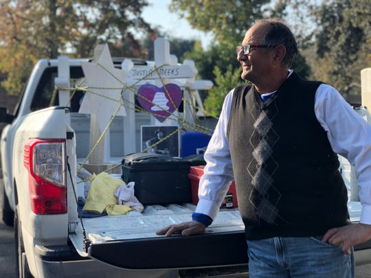Greg Zanis stands outside his pickup truck in Thousand Oaks, California, Sunday morning. He travelled there overnight to deliver crosses for the mass shooting. Next, he's going to deliver more for victims of the state's fires.