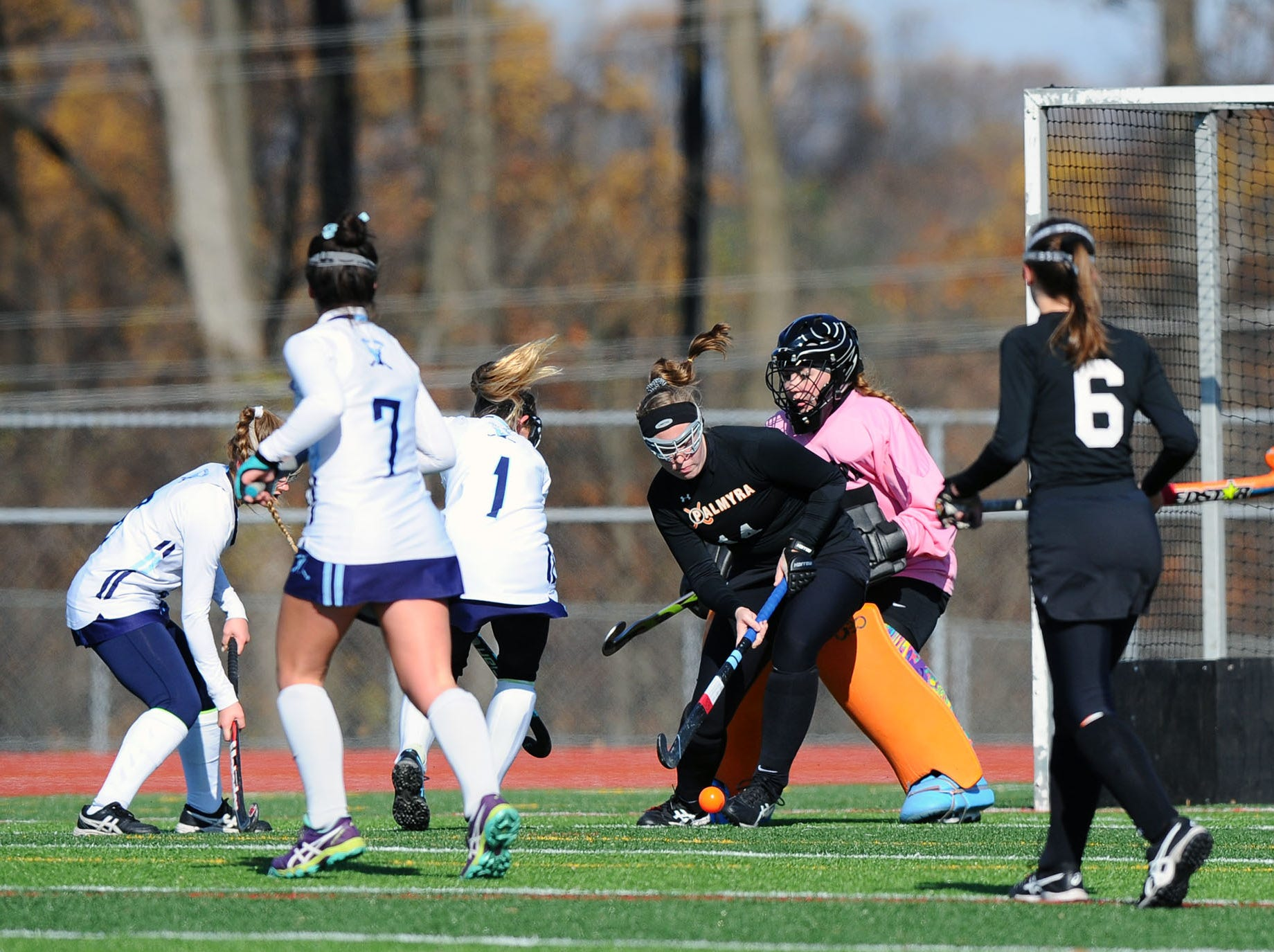 Palmyra's Emily Risser (14) clears the ball in front of her (GK) Ashton Byrd during the first half of play.