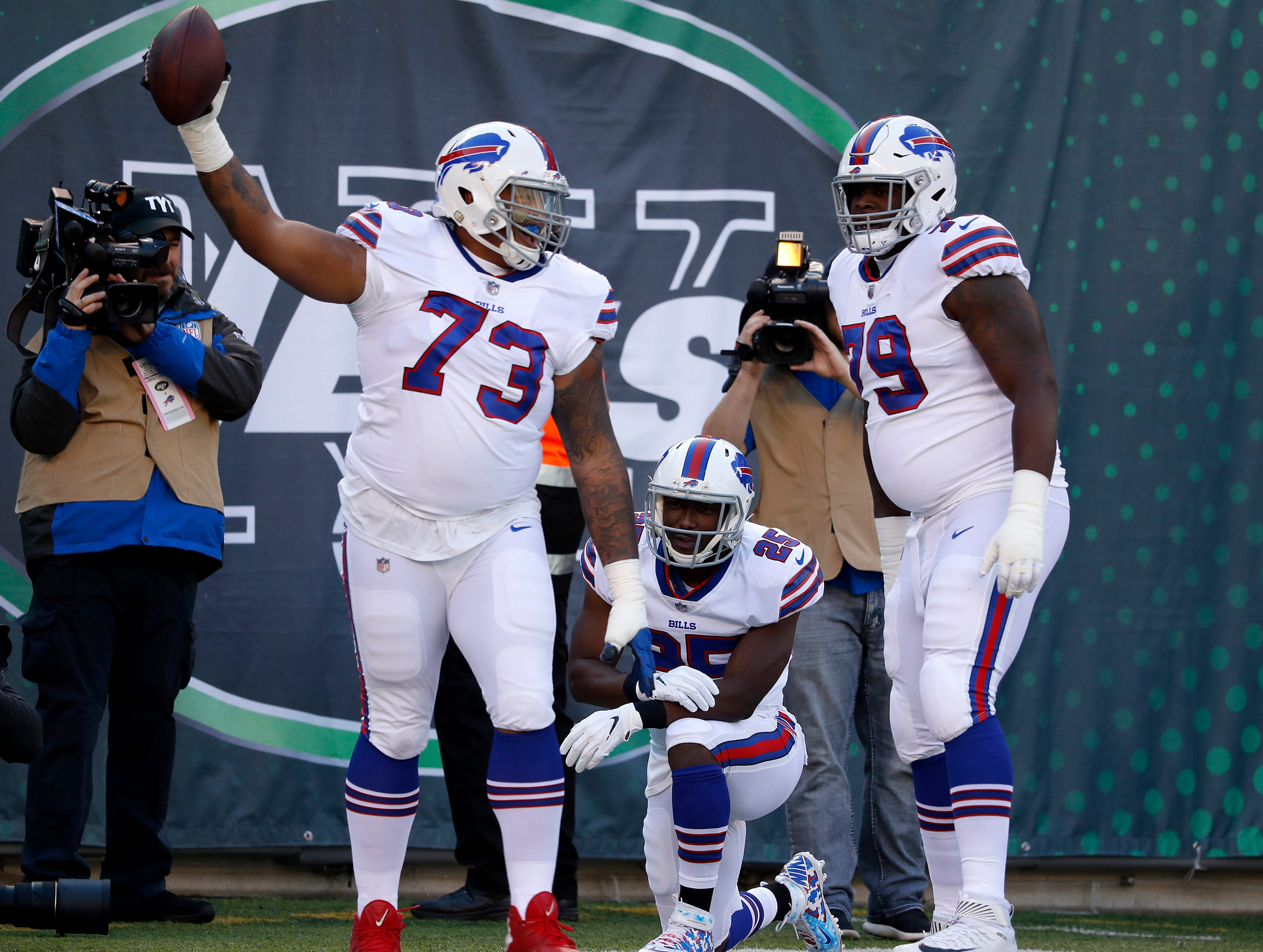EAST RUTHERFORD, NEW JERSEY - NOVEMBER 11: LeSean McCoy #25 of the Buffalo Bills is congratulated by his teammates Dion Dawkins #73 and Jordan Mills #79 after his first quarter touchdown against the New York Jets at MetLife Stadium on November 11, 2018 in East Rutherford, New Jersey. (Photo by Michael Owens/Getty Images)