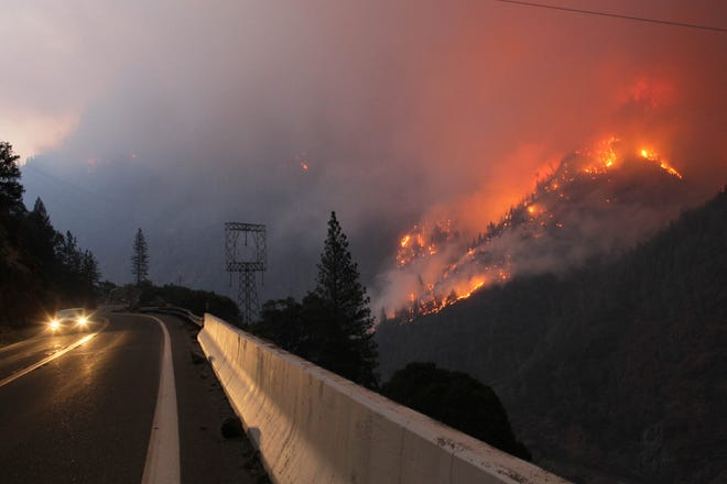 Sunday morning, a Cal Fire vehicle drives along Highway 70 as the Camp Fire continues to burn on the ridge line east of the roadway.