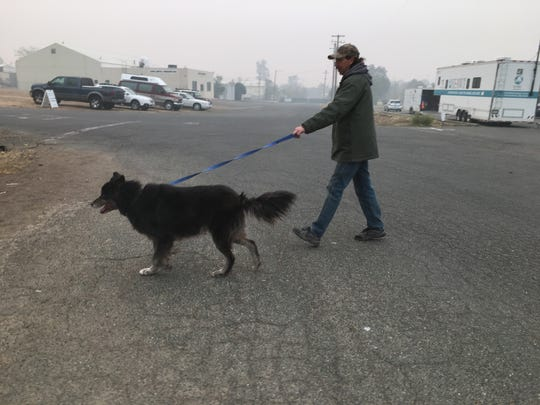 Jon Trojanowski, a volunteer with North Valley Animal Disaster Group, walks his Malamue-Lab mix Lexi.  Trojanowski lost his home in the Camp Fire but remained on task volunteering to help aid and rescue animals endangered by the fire.