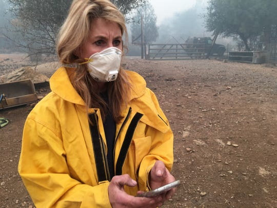 North Valley Animal Disaster Group volunteer Lori Finch verifies the number of animals on a farm that's been evacuated for the Camp Fire. Finch provides the information to the owner.