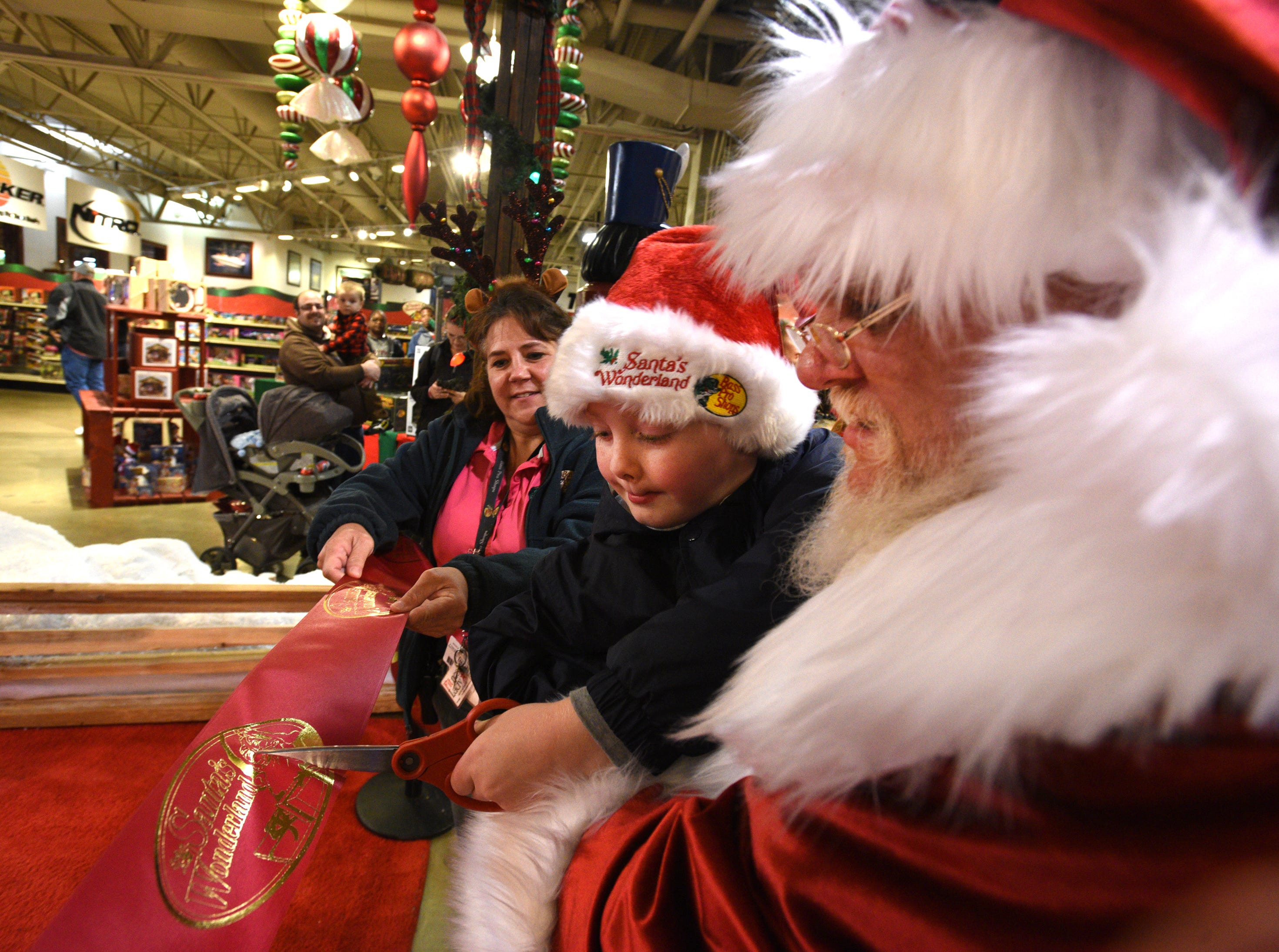 Santa and friend cut the ribbon for his Wonderland after the Bass Pro Shops-Louisiana Boardwalk Outlets Santa Parade.