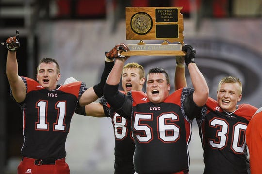 Brandon Valley's Cole Siegfried, from left, Carter Olthoff, Jack Harvison and Andrew Hanson hold up the 11AAA championship trophy after their win against Washington Saturday, Nov. 10, at the DakotaDome in Vermillion.