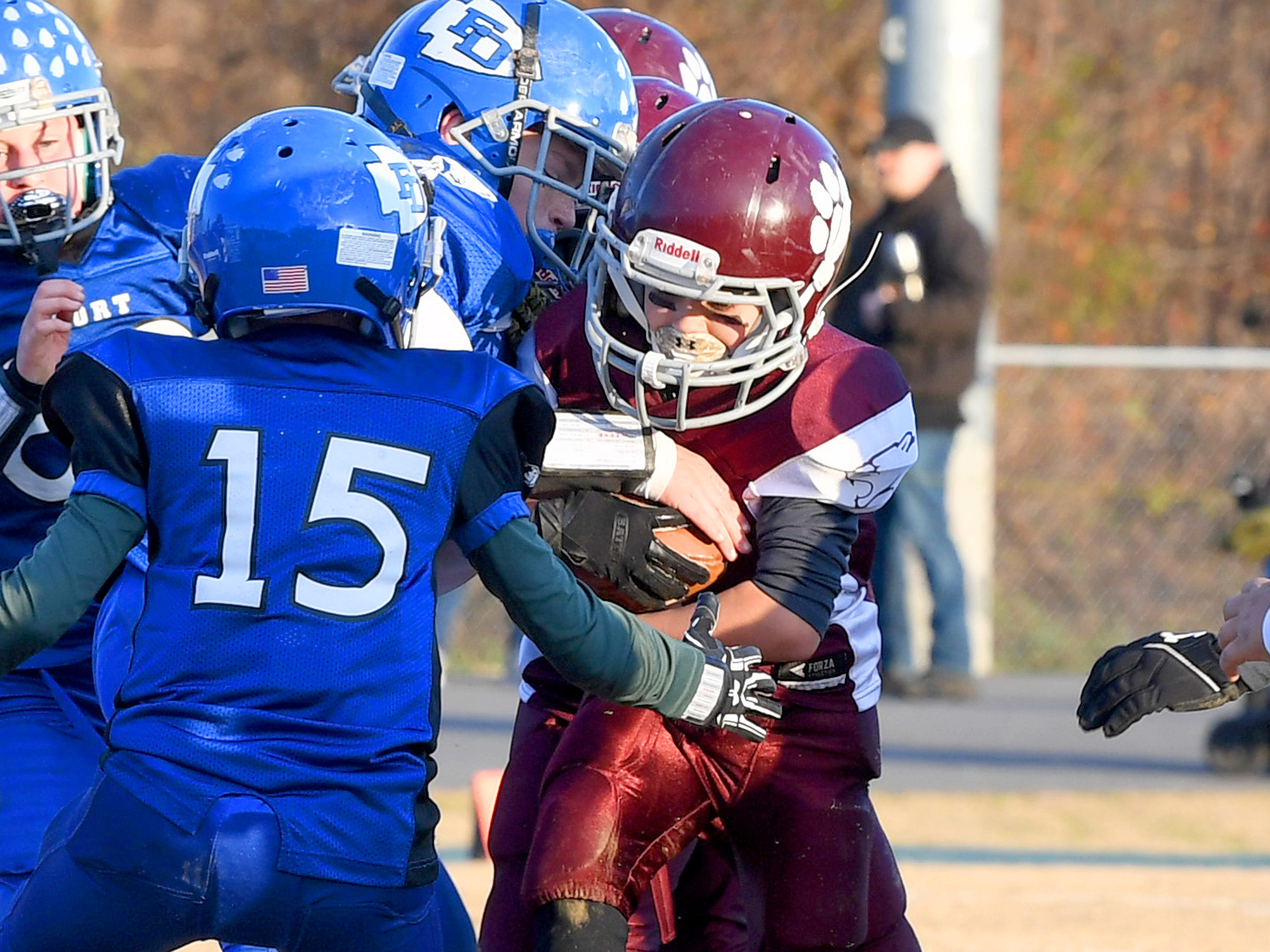 A Stuarts Draft player protects the ball as he is tackled during the Augusta County Quarterback Club Juniors Super Bowl in Fishersville on Sunday, Nov. 11, 2018.  Fort Defiance beats Stuarts Draft, 13-12.
