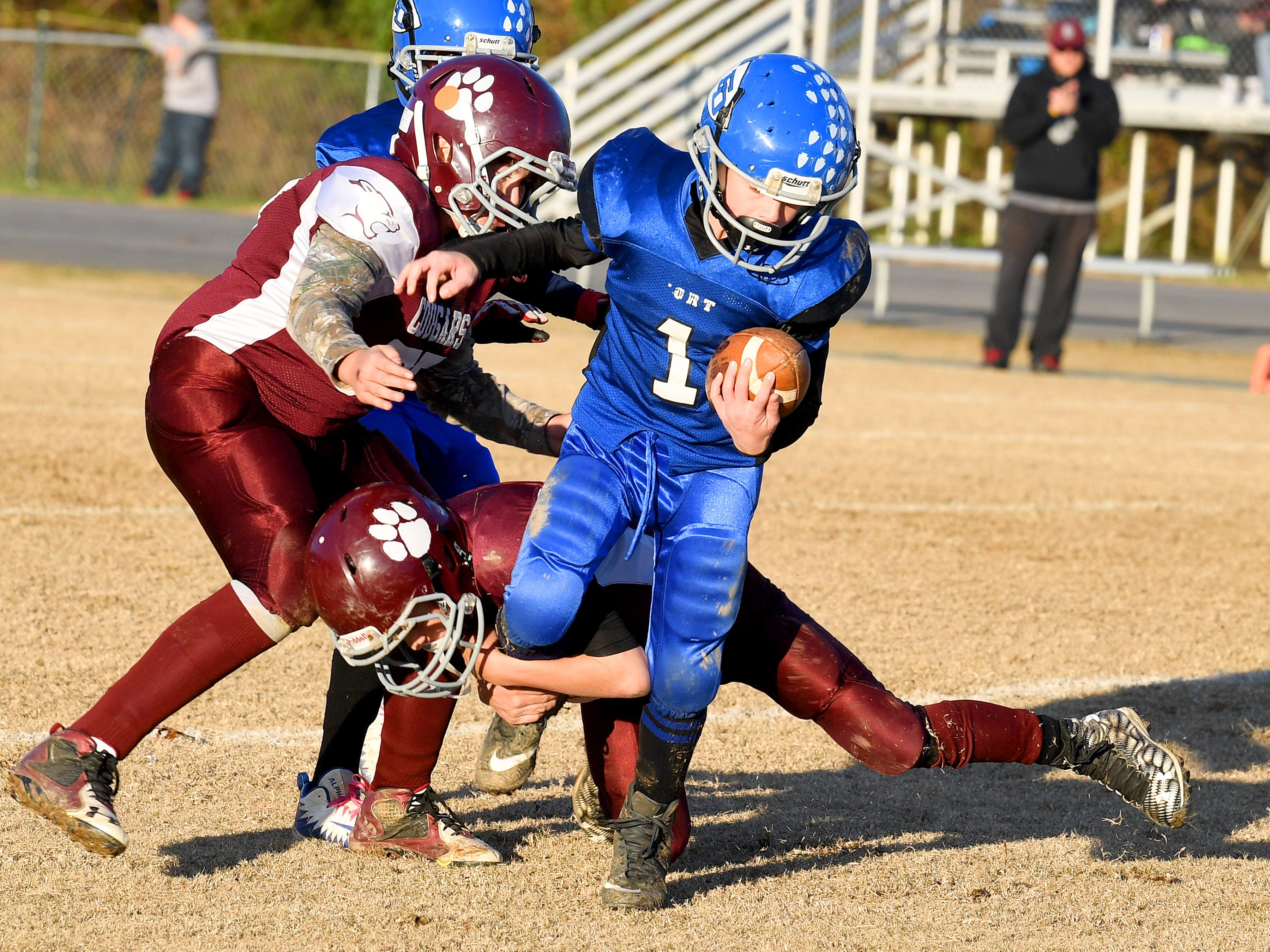 Fort Defiance's Bradley Hebb struggles to keep moving with the ball as he is wrapped up around the leg during the Augusta County Quarterback Club Juniors Super Bowl in Fishersville on Sunday, Nov. 11, 2018. Fort Defiance beats Stuarts Draft, 13-12.