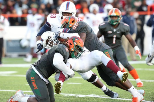 FAMU linebacker Jibreel Hazly (2) and defensive tackle Renaldo Flowers converge to make a tackle against South Carolina State. Hazly recently played in the FCS National Bowl.