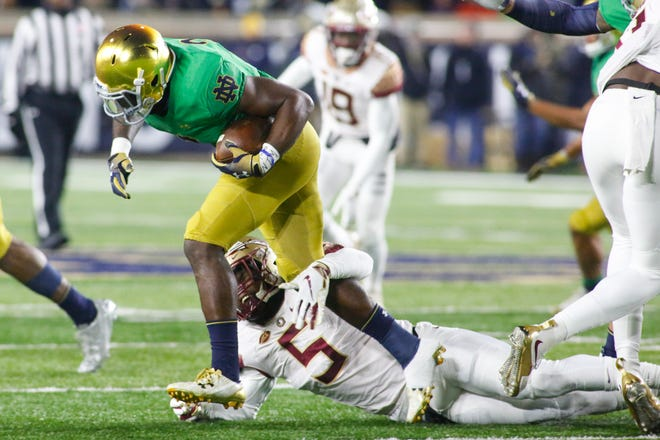 Florida State junior linebacker Dontavious Jackson, 5, drags down Notre Dame senior running back Dexter Williams during the third quarter in South Bend on Saturday.