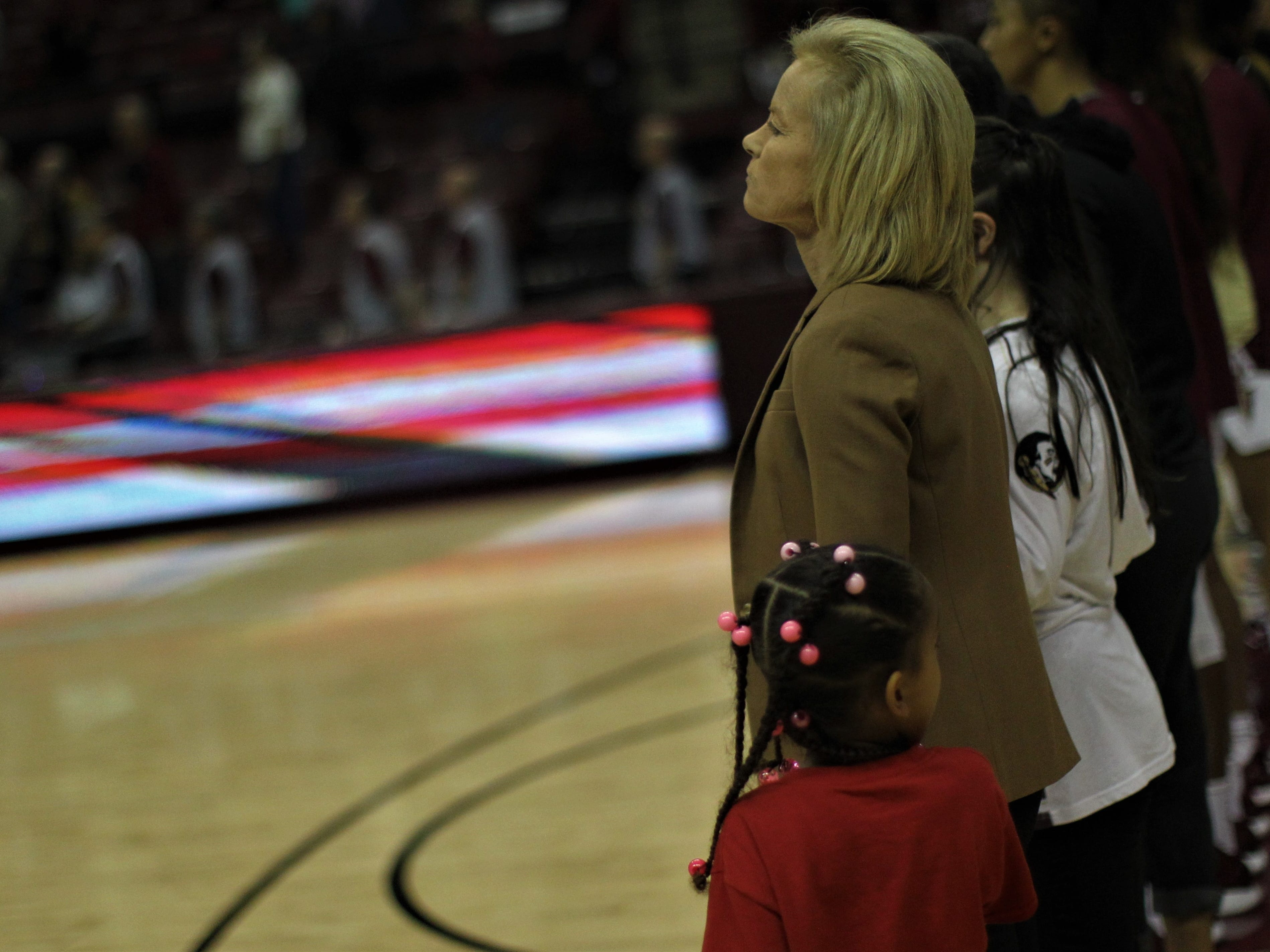 Florida State women's basketball coach Sue Semrau stands at attention during the national anthem, prior to the Seminoles' game against Florida at the Tucker Civic Center on Nov. 11, 2018.