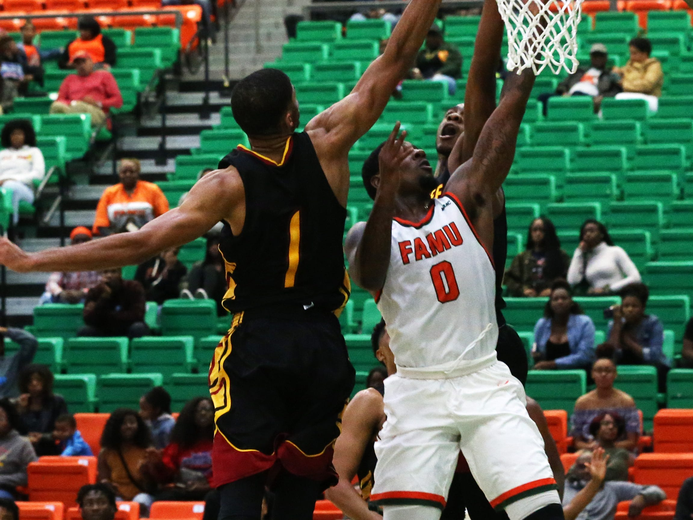 Florida A&M Rattlers forward Tracy Hector Jr. (0) scores over two Tuskegee Golden Tigers in their first home game of the season on Saturday, Nov. 10.
