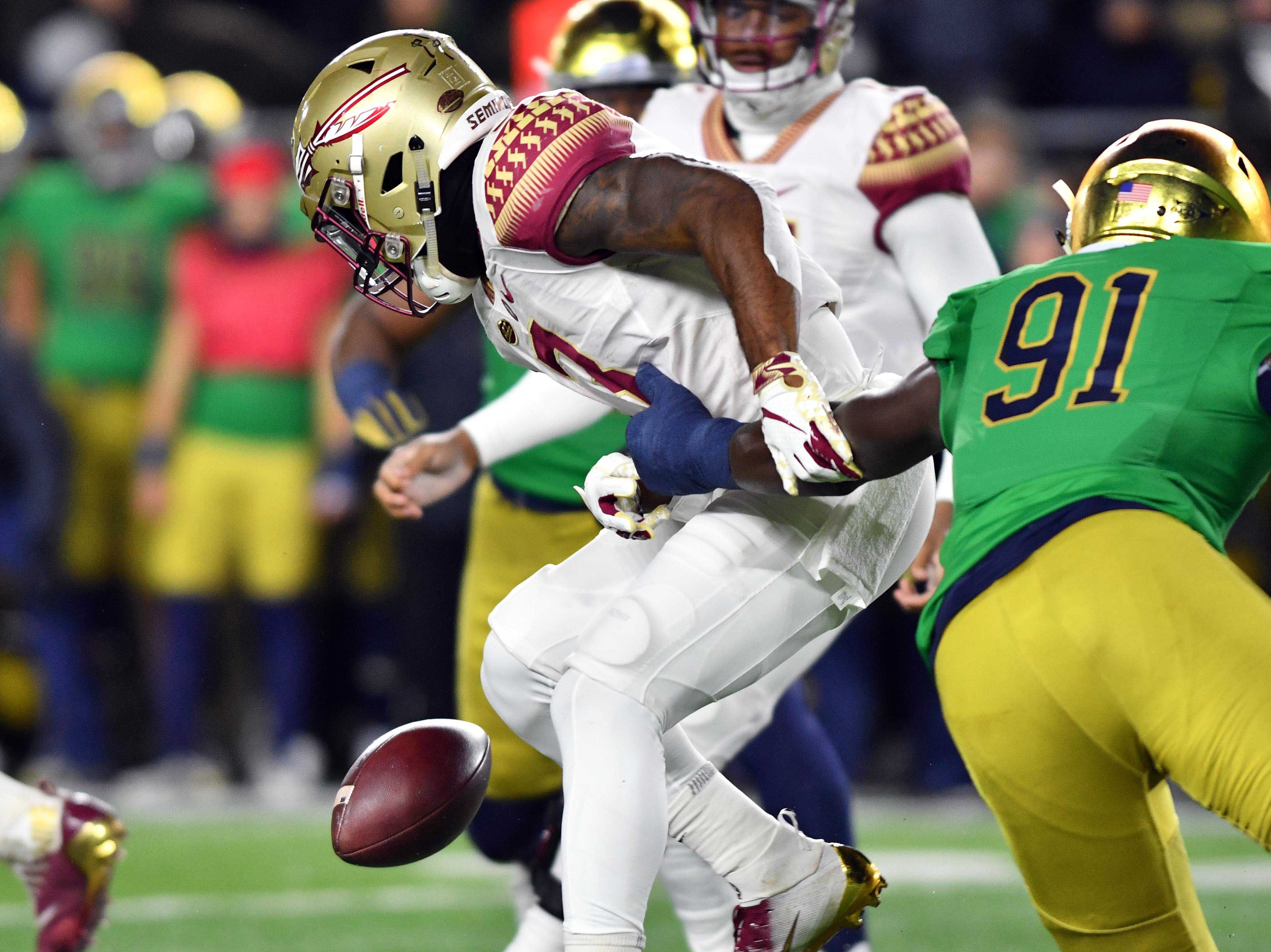 Nov 10, 2018; South Bend, IN, USA; Notre Dame Fighting Irish ddefensive lineman Adetokunbo Ogundeji (91) strips the ball from Florida State Seminoles running back Cam Akers (3) in the first quarter at Notre Dame Stadium. Mandatory Credit: Matt Cashore-USA TODAY Sports