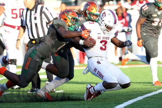 FAMU defensive back Terry Jefferson (1) linebacker Jibreel Hazly (2) tackle the S.C. State quarterback Tyrece Nick.