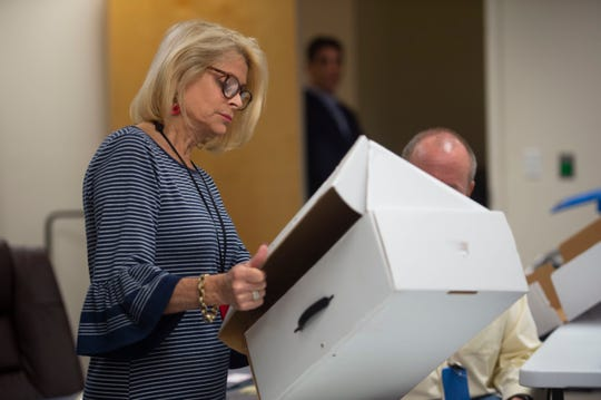 Indian River County Supervisor of Elections Leslie Sawn helps counts ballots Sunday, Nov. 11, 2018, at the elections office in Vero Beach.