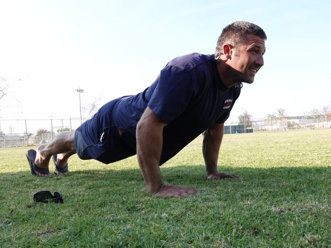 """After more than two days without sleep, firefighter Nathan Kidd of the Cathedral City Fire Department ran 5 miles and did push ups at a command post at the Camarillo Airport while taking a break from the Woolsey Fire. """"It just helps me relax,"""" he said."""