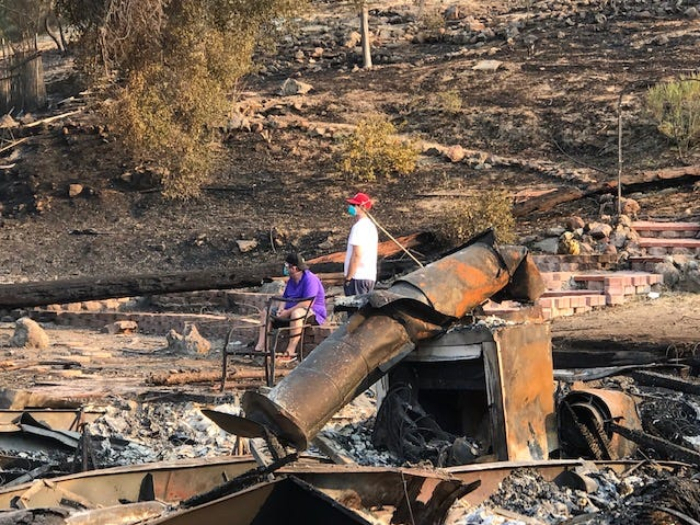 Residents of Oak Forest Estates in Westlake Village and their friends survey the rubble left behind Saturday by the Woolsey Fire. Some residents estimated 25 homes were destroyed or damaged by the blaze.
