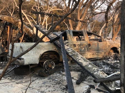 A burnt-out truck lies in ashes in Oak Forest Estates in Westlake Village on Saturday after the Woolsey Fire passed through. Some residents estimated 25 homes were destroyed or damaged by the blaze.