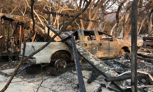 A burnt-out truck lies in ashes in Oak Forest Estates in Westlake Village after the Woolsey Fire passed through.