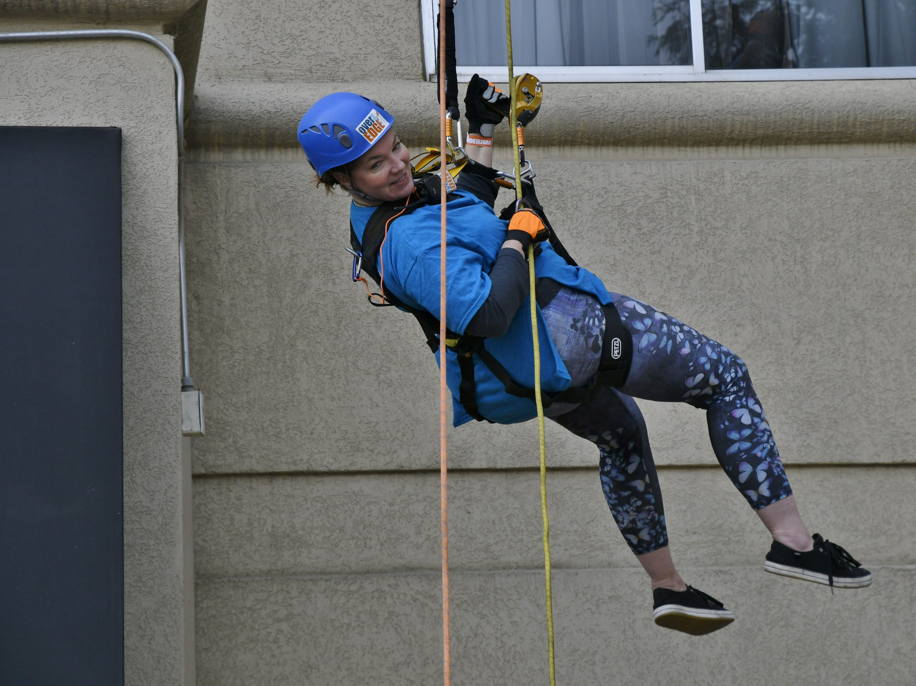 Dana Galante rappels down the side of the Visalia Marriott at the Convention Center in downtown Visalia for the first Over the Edge fundraising event for The Source LGBT+ Center on Saturday, November 10, 2018.