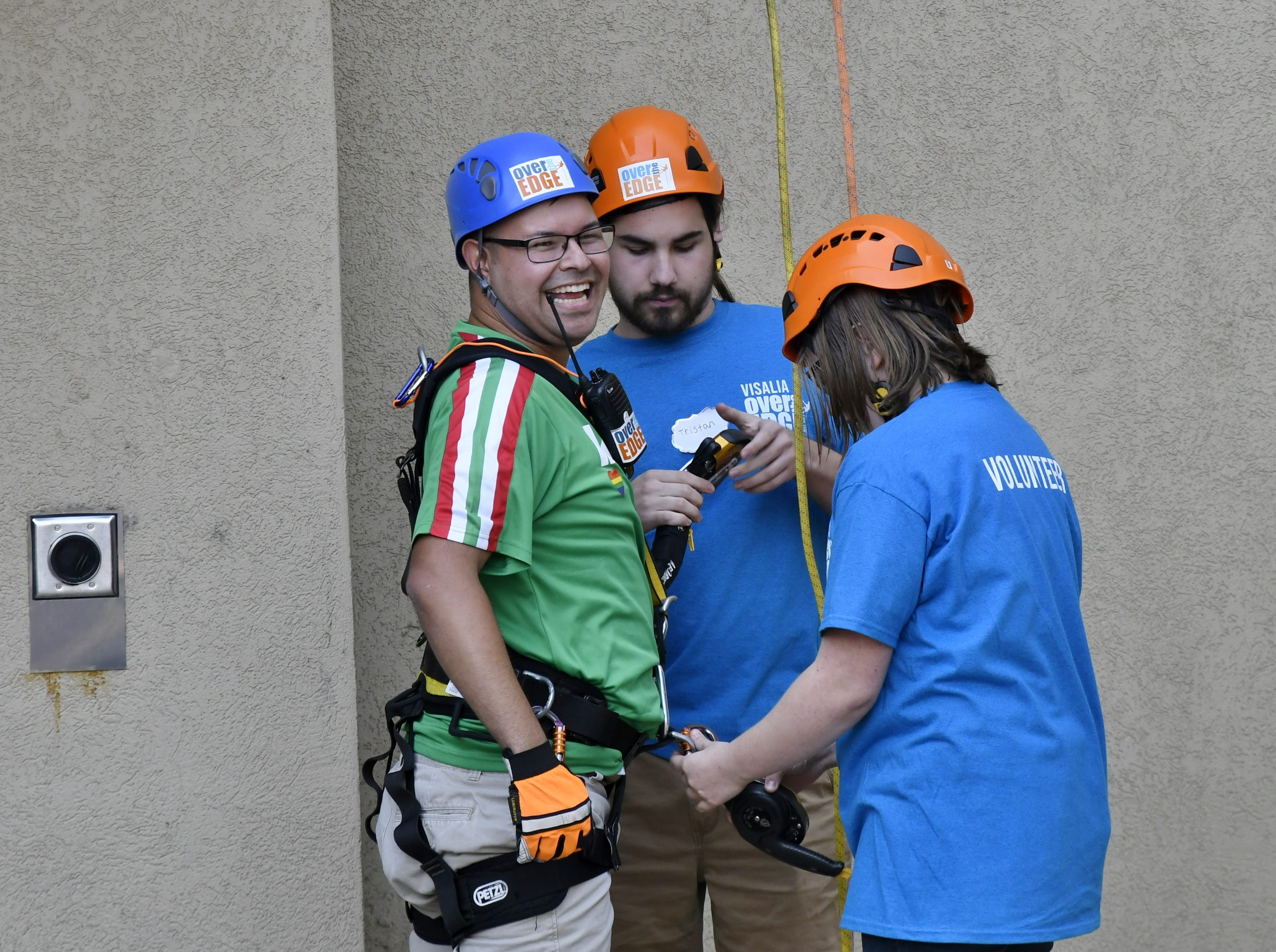 Carlos Mendoza smiles after rappelling down the side of the Visalia Marriott at the Convention Center in downtown Visalia for the first Over the Edge fundraising event for The Source LGBT+ Center on Saturday, November 10, 2018.