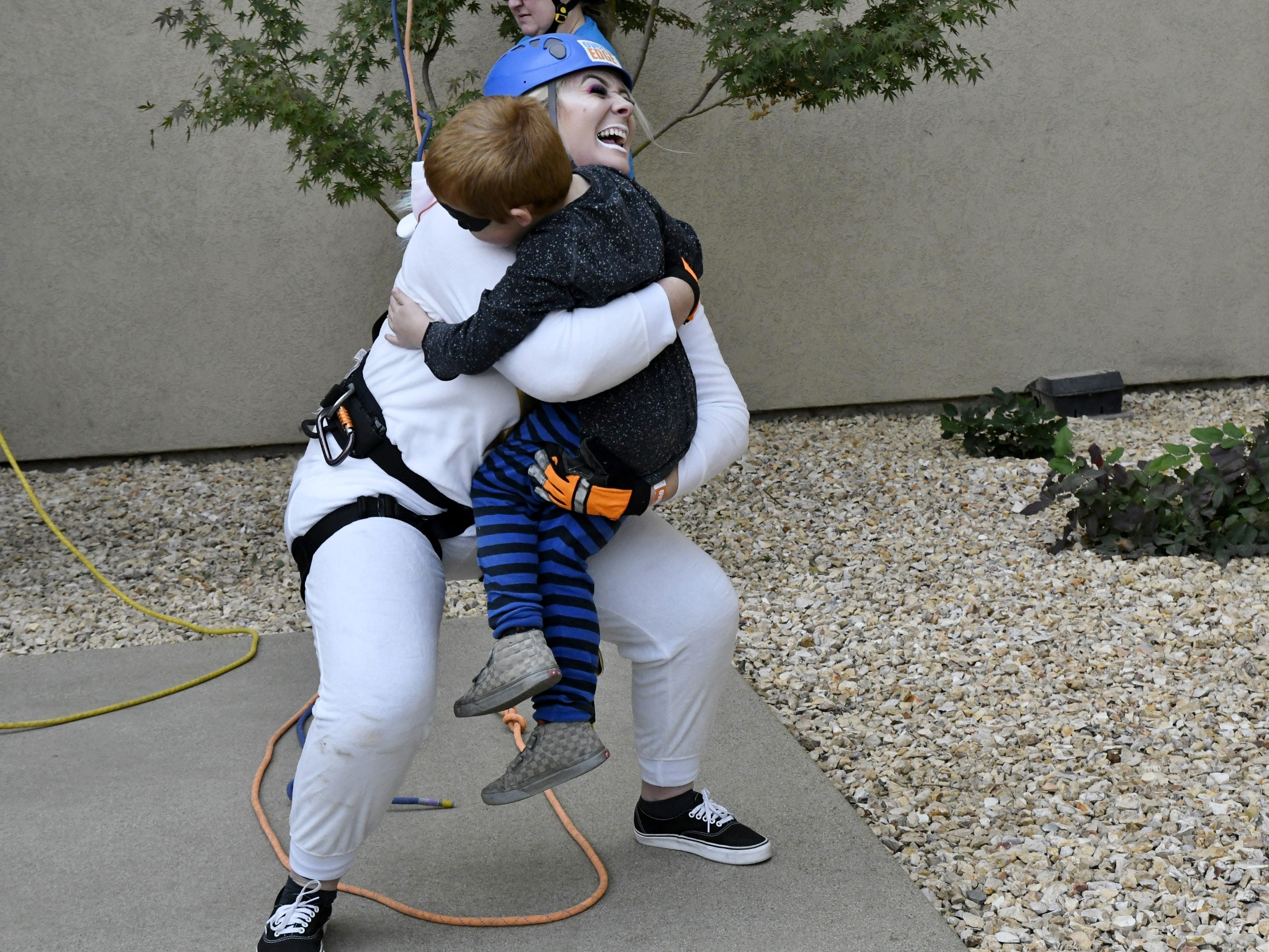 Katie McDonald embraces son Bentley McReynolds after she finishes her rappel down the side of the Visalia Marriott at the Convention Center in downtown Visalia for the first Over the Edge fundraising event for The Source LGBT+ Center on Saturday, November 10, 2018.