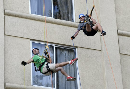 Carlos Mendoza (left) and Alex Guitierrez rappel down the side of the Visalia Marriott at the Convention Center in downtown Visalia for the first Over the Edge fundraising event for The Source LGBT+ Center on Saturday, November 10, 2018.
