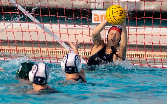 Redwood's Jada Griffith blocks a Porterville shot in a Central Section Division II girls water polo championship on Saturday, November 10, 2018.