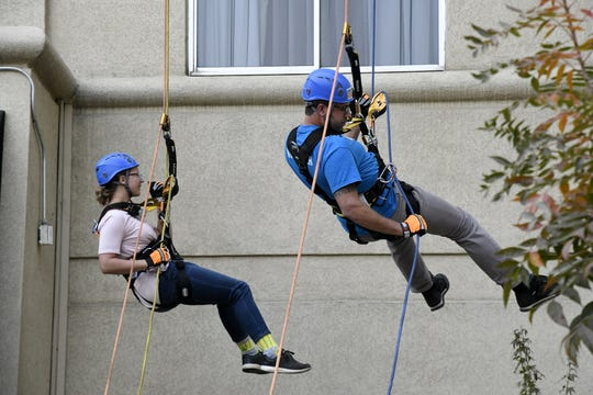 Mary West and Geoff Koch rappel down the side of the Visalia Marriott at the Convention Center in downtown Visalia for the first Over the Edge fundraising event for The Source LGBT+ Center on Saturday, November 10, 2018.