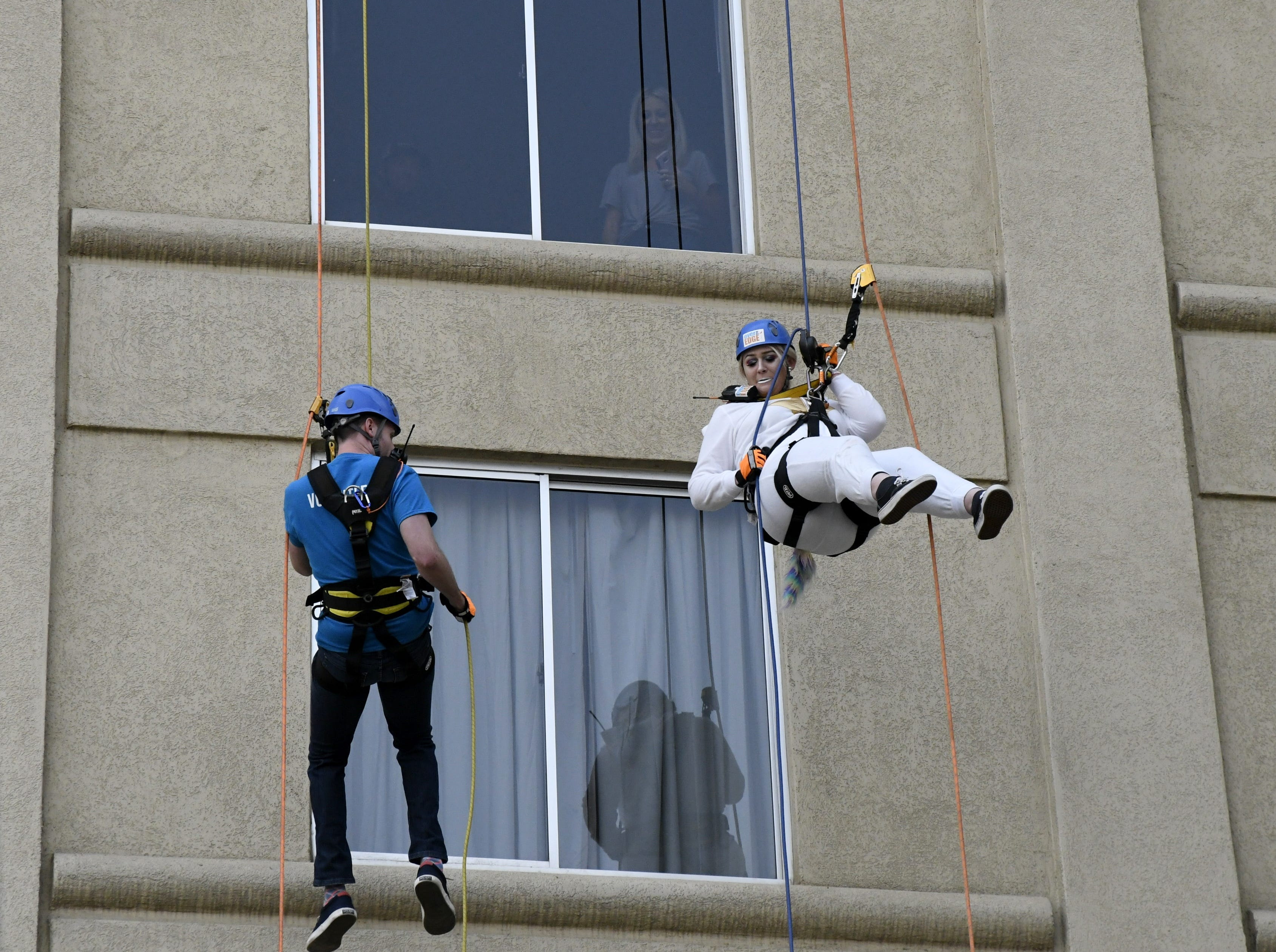 Bradley Rutledge (left) and Kayie McDonald rappel down the side of the Visalia Marriott at the Convention Center in downtown Visalia for the first Over the Edge fundraising event for The Source LGBT+ Center on Saturday, November 10, 2018.