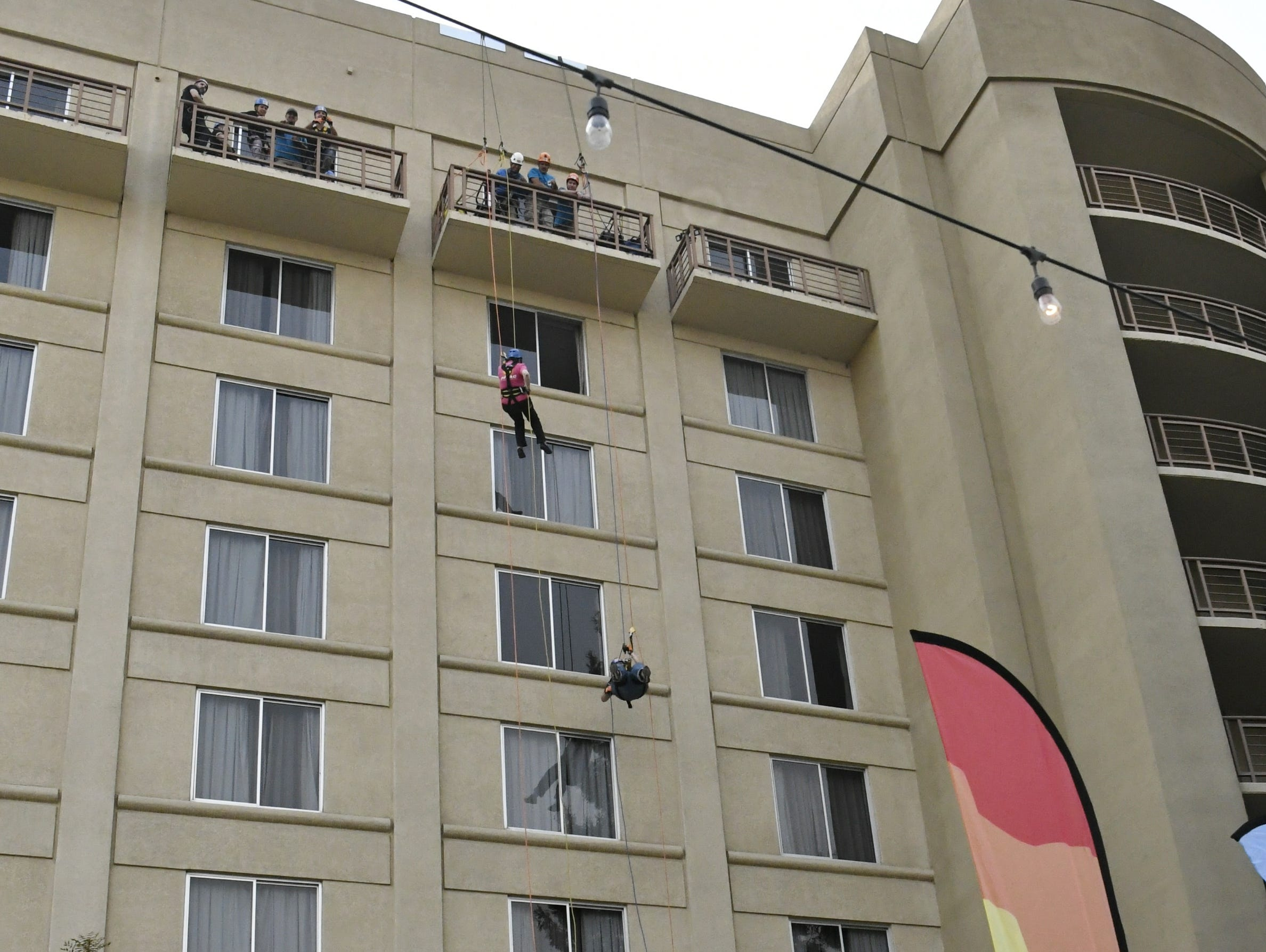 Family members cheer on Kathryn Hall and Ry Ginsburg as they rappel down the side of the Visalia Marriott at the Convention Center in downtown Visalia for the first Over the Edge fundraising event for The Source LGBT+ Center on Saturday, November 10, 2018.