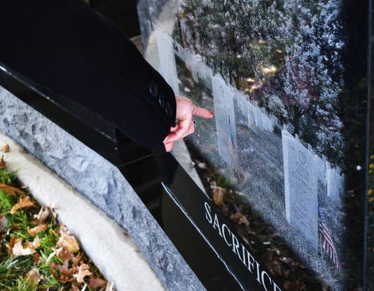 Judy Campbell, chair of the Gold Star Memorial Finance Committee, points to three gravestones inscribed on the new monument. The image is from a picture of her brother, boyfriend and friend's gravestones in Arlington Cemetery.