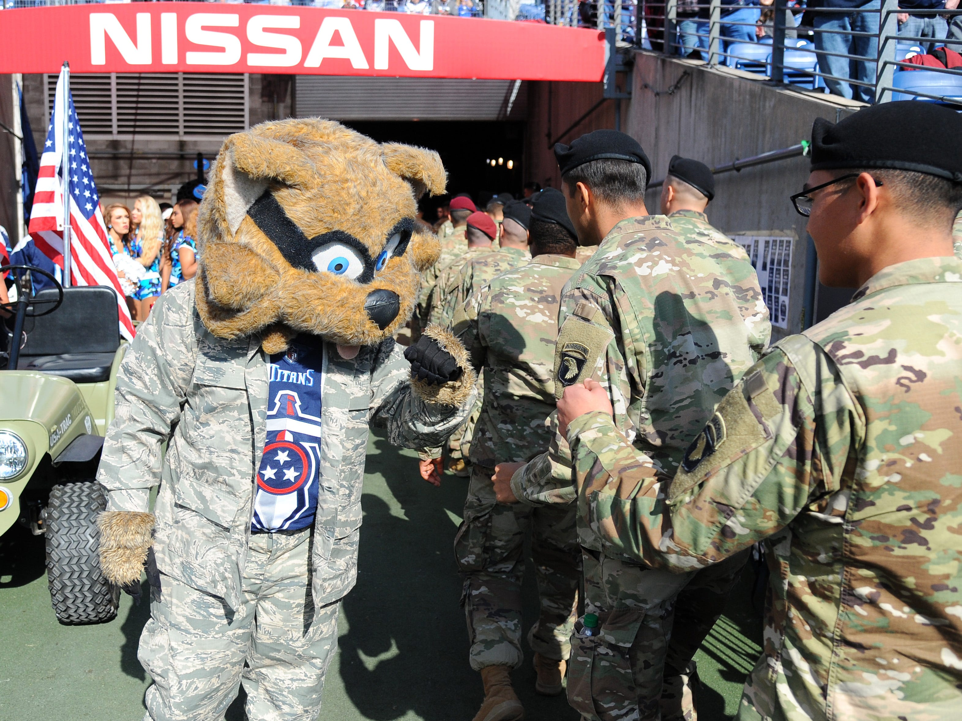 Titans mascot T-Rac slaps hands with members of the armed forces.