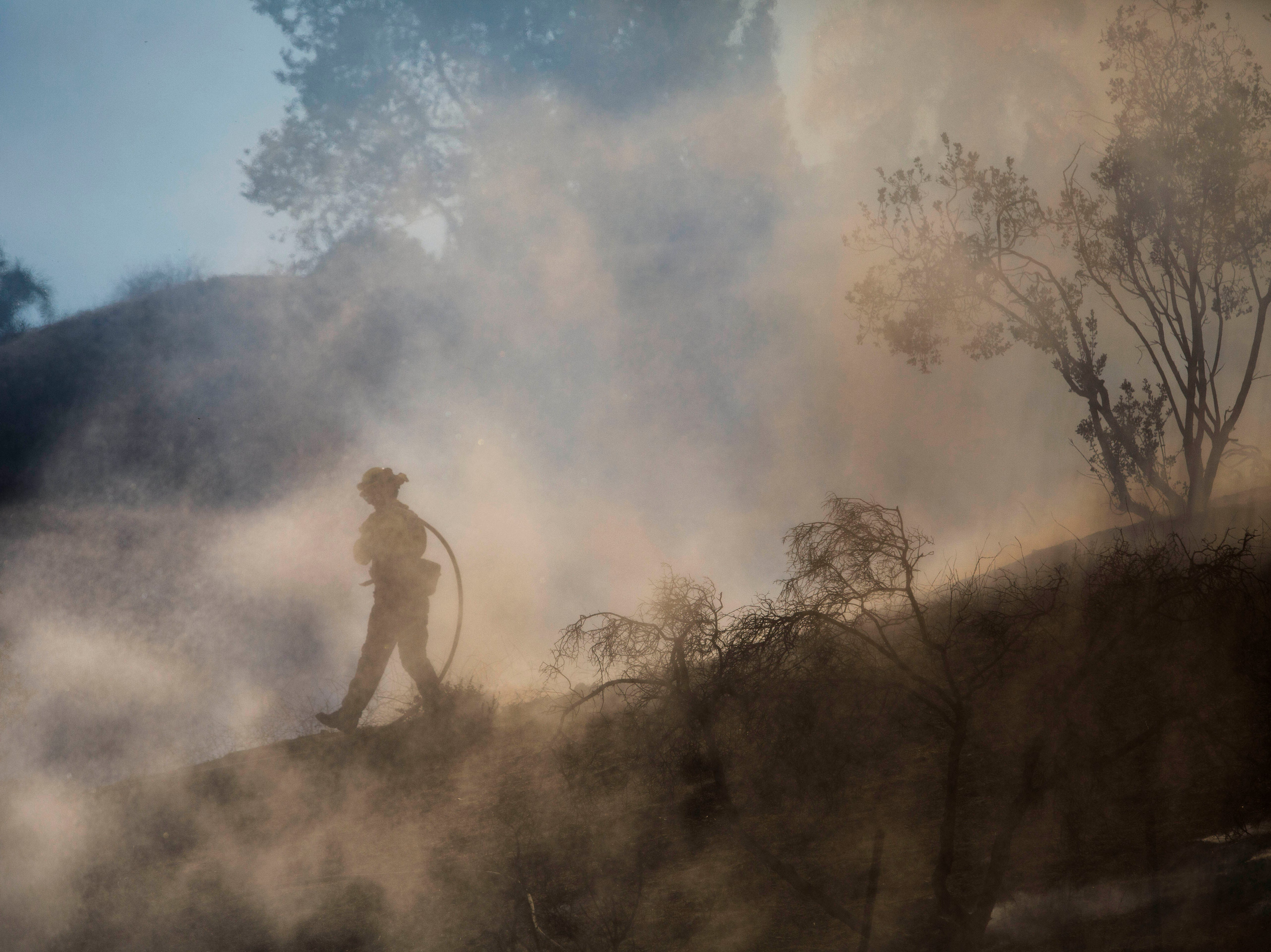 Firefighters put out flareup on a hill in West Hills during the Woolsey Fire in Southern California on Nov. 10, 2018.