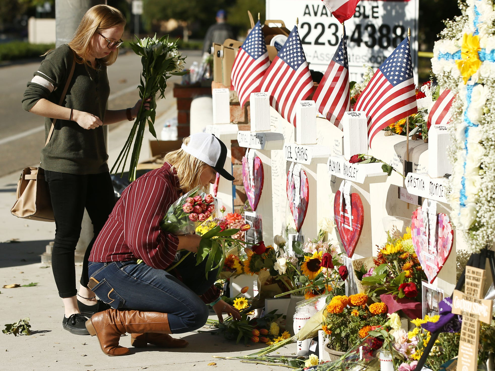 People pay their respects and bring flowers to the memorial to victims of the Borderline Bar and Grill massacre.