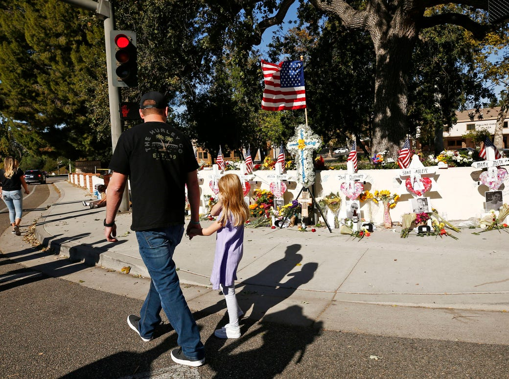 A man and childe observe the mass shooting victims' memorial grows as the FBI and Ventura County Sheriff's office continue their investigation at the Borderline Bar and Grill on Sunday.