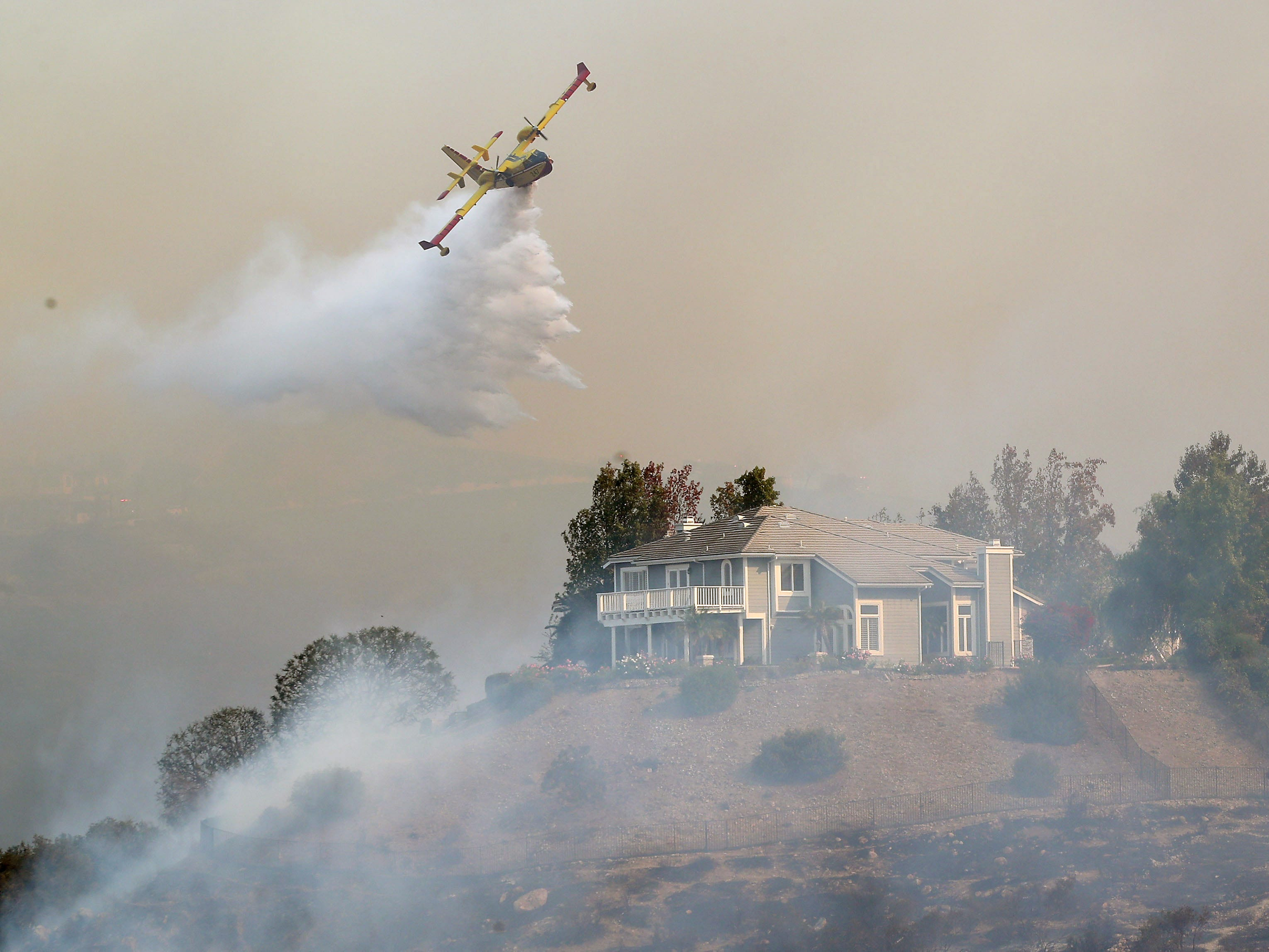 A firefighting air tanker is used to fight the Woolsey Fire as it threatens hillside homes in Westlake Village, Ca., Nov. 9, 2018.