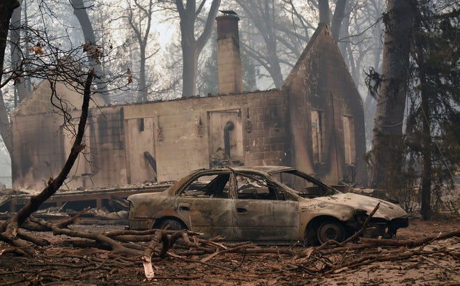 Smoke clouds the air above the remains of a burned-out house and car in Paradise, California, following the Camp Fire devastation.