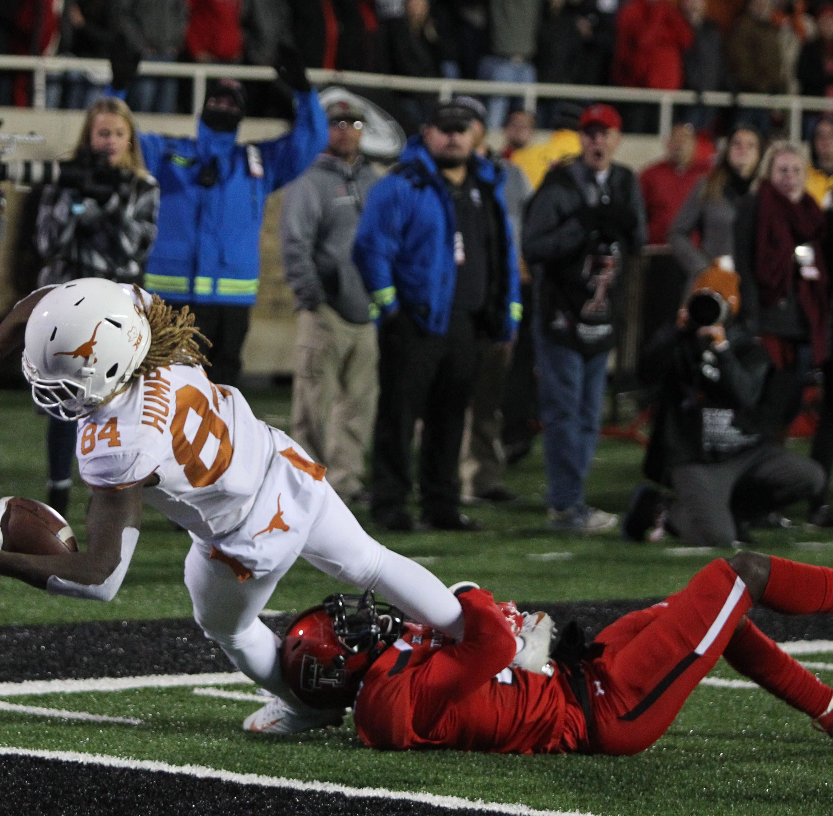Texas Longhorns wide receiver Lil'Jordan Humphrey (84) lunges for the end zone over Texas Tech Red Raiders defensive back Demarcus Fields (23) to score the winning touchdown late in the fourth quarter at Jones AT&T Stadium.