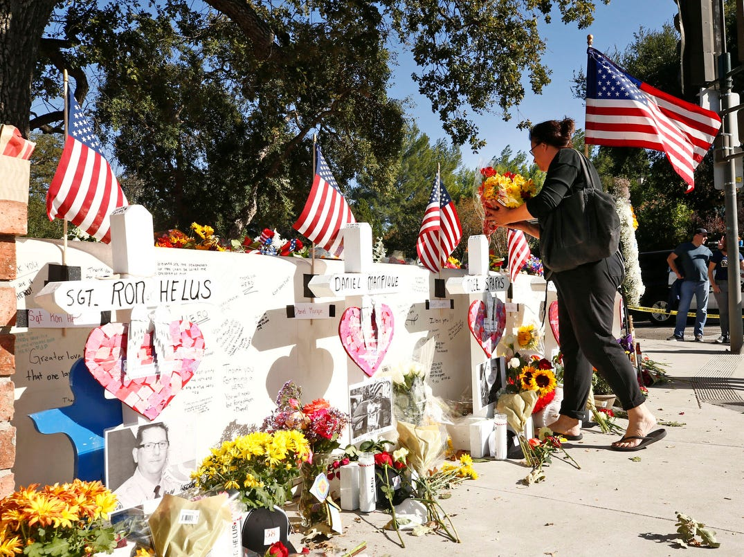People bring tributes to the mass shooting victims memorial on Sunday, Nov. 11, 2018, in Thousand Oaks, Calif.