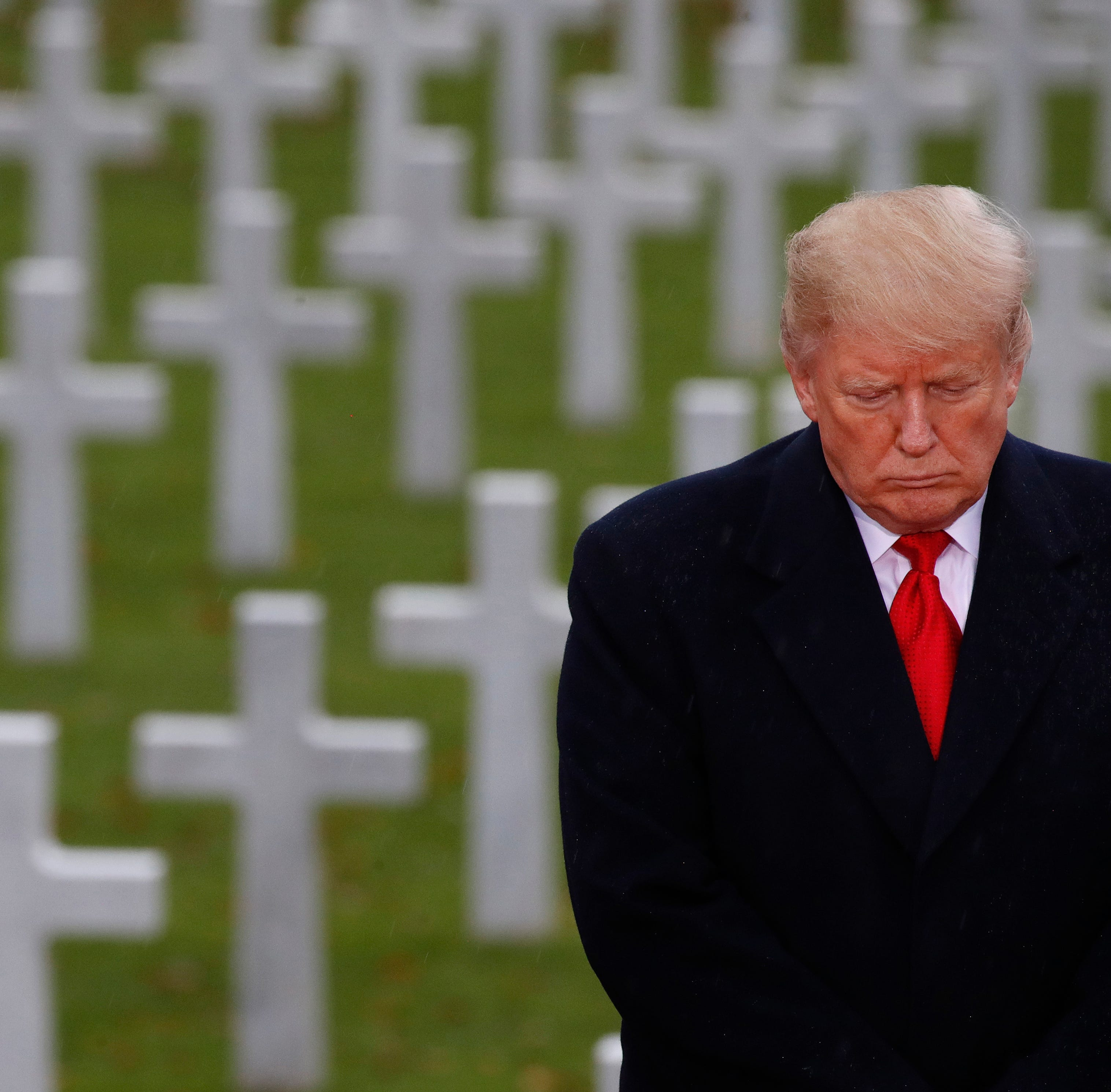 President Donald Trump stands in front of headstones at Suresnes American Cemetery near Paris.