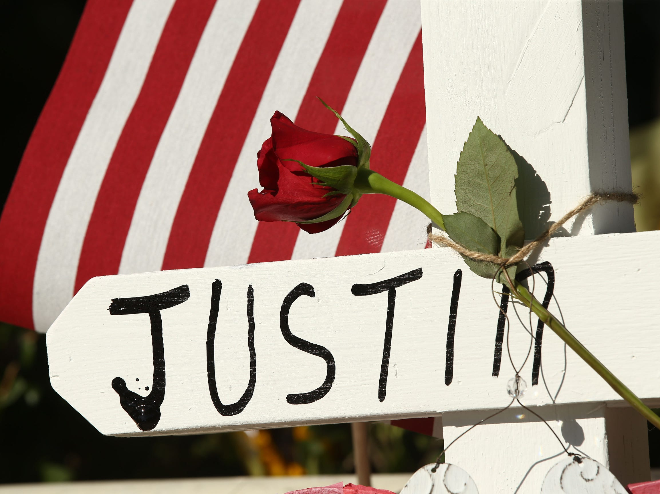 A rose sits atop the cross for Justin Meeks, as the mass shooting victims memorial grows in Thousand Oaks, Calif. Twelve people were shot and killed Wednesday by gunman Ian David Long who opened fire at the Borderline Bar and Grill.