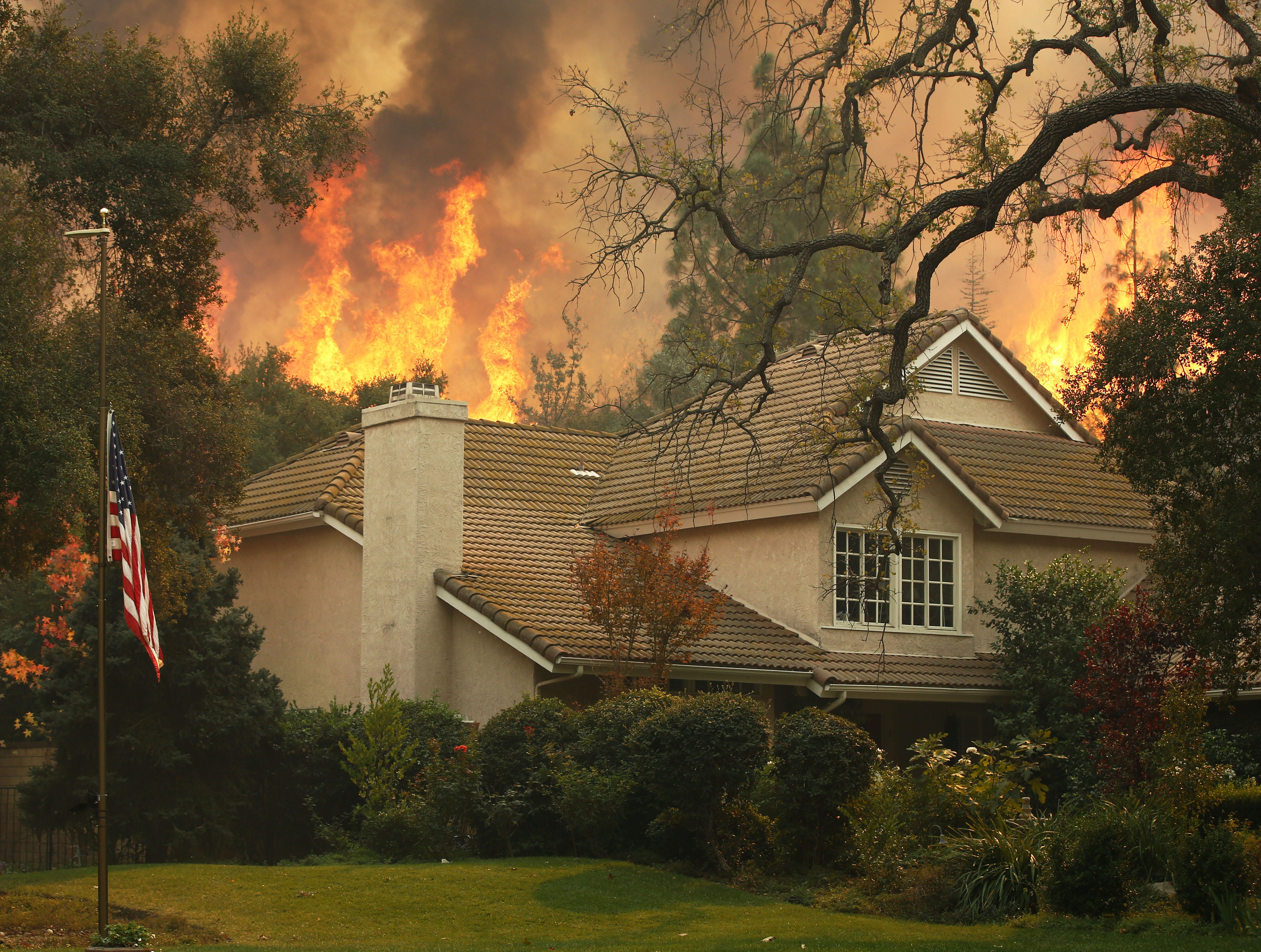 A U.S. flag is displayed at half-staff to honor the shooting victims as the Woolsey fire burns on the hill behind a home in Westlake Village. Twelve people were shot and killed Wednesday by gunman Ian David Long who opened fire at the Borderline Bar and Grill.