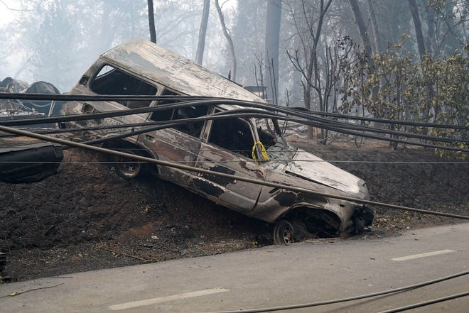 Nov 10, 2018; Paradise, CA, USA; An abandoned SUV, crashed over an embankment and covered in downed power lines, pays silent testament to the frantic escape from the Camp Fire in Paradise, California Mandatory Credit:  Trevor Hughes-USA TODAY ORIG FILE ID:  20181110_ajw_usa_269.jpg